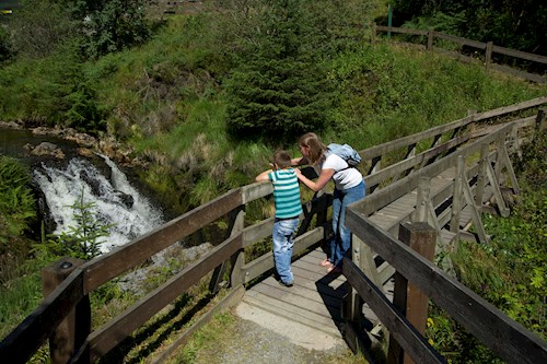 Mother and child watching the waterfall from a bridge