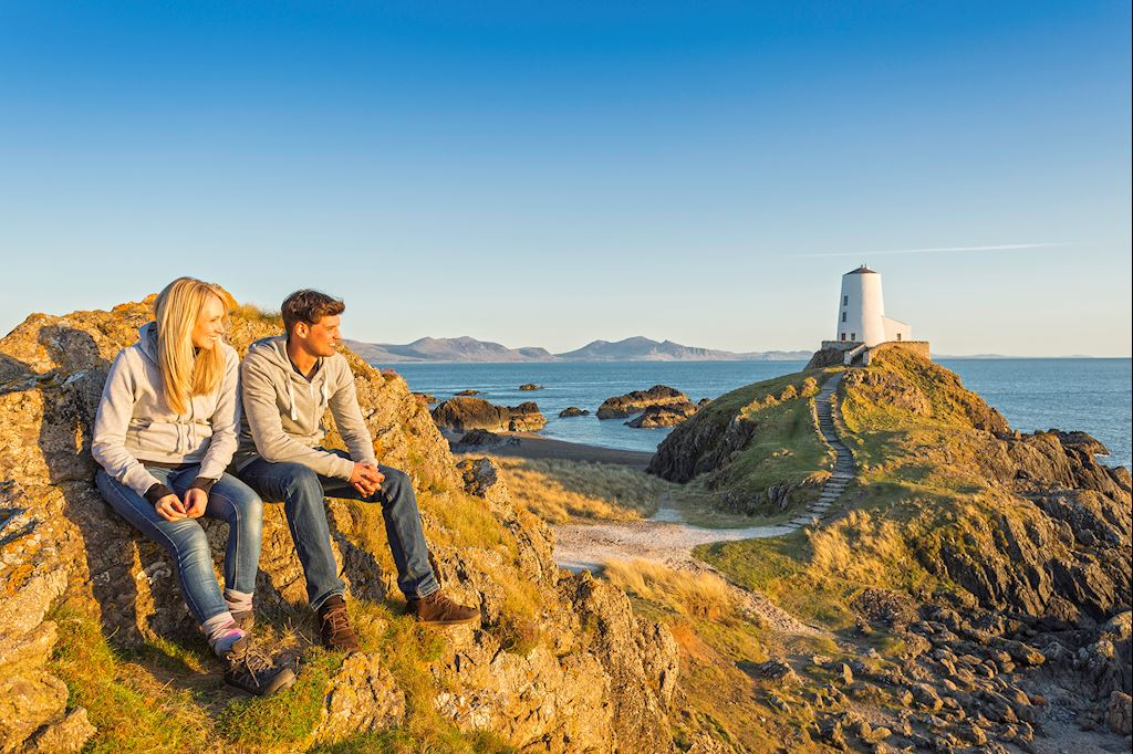 Couple sitting on rocks near Llanddwyn island