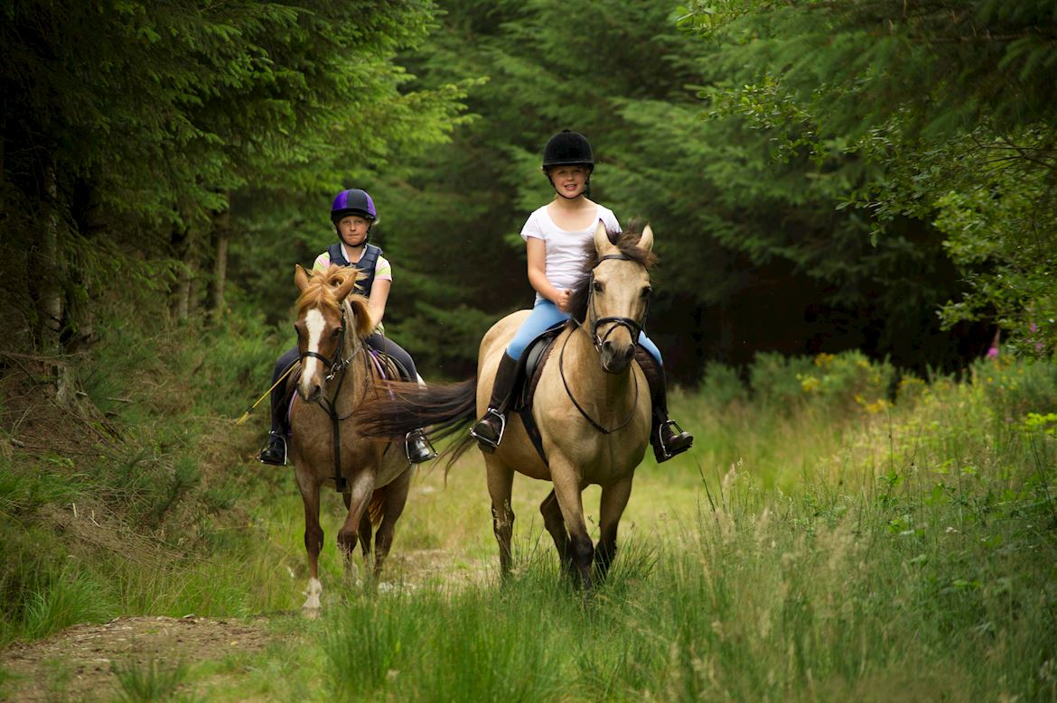 Two young women riding their horses through Dyfnant Forest
