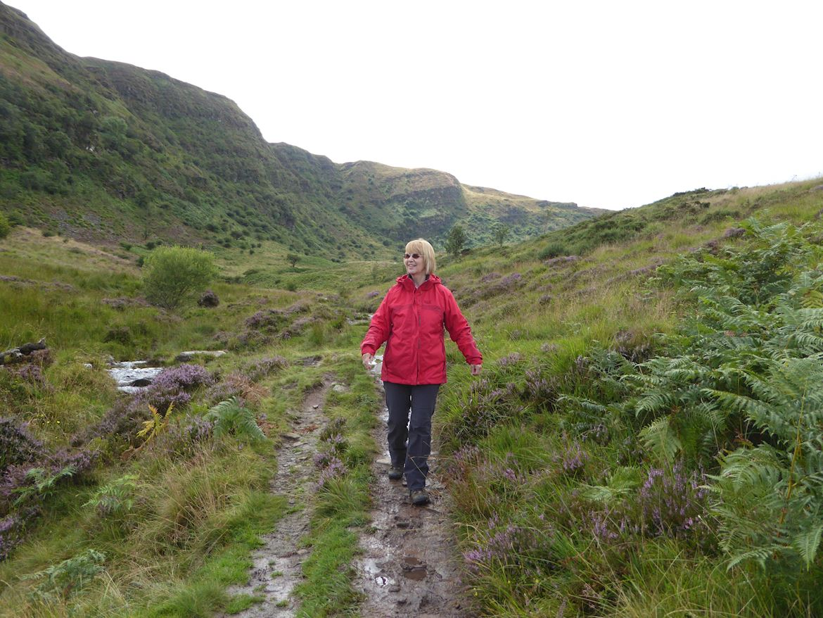 Woman walking along a trail at Craig Cerrig Gleisiad a Fan Frynych National Nature Reserve